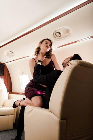seductive, elegant girl with closed eyes sitting on mans laps in plane