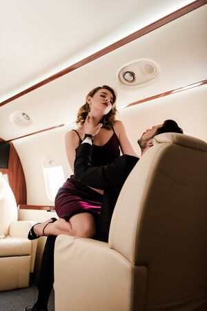 seductive, elegant girl with closed eyes sitting on mans laps in plane