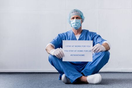 mature doctor in medical mask and cap holding placard with i stay at work for you, you stay at home for us lettering while sitting on white Foto de archivo