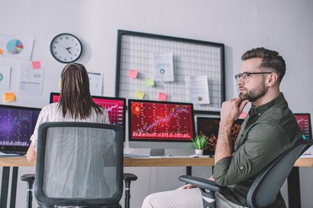 Pensive data analyst looking away near colleague working with computers in office