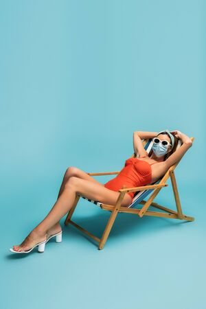 Woman in sunglasses and medical mask sitting on deckchair on blue Stock Photo