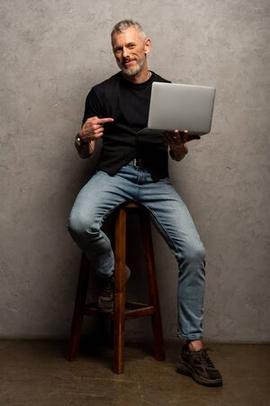 happy man pointing with finger at laptop and looking at camera on grey