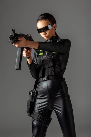 futuristic african american woman in glasses aiming assault rifle isolated on grey