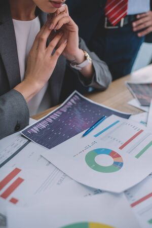 Cropped view of data analysts working with charts on table