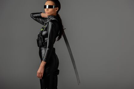 side view of futuristic african american woman in glasses with sword on grey