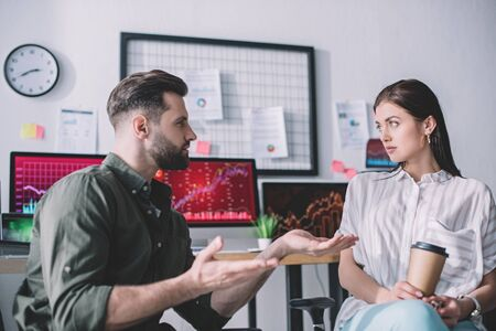 Data analyst planning work with colleague holding paper cup in office