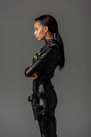 side view of serious attractive futuristic african american woman isolated on grey