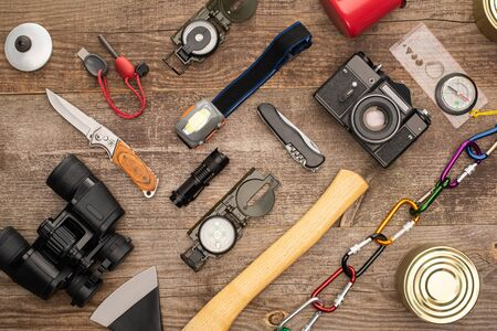 top view of photo camera, tin cans and hiking equipment on wooden surface