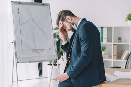 side view of stressed businessman standing with bowed head and closed eyes near flipchart with graphs showing recession