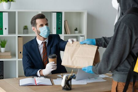 partial view of food delivery man giving paper bag to businessman in medical mask in office