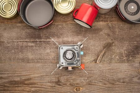 top view of tin cans, gas-burner, metal dishes and cup on wooden surface