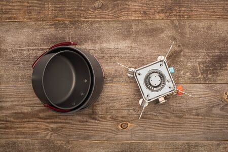 top view of gas burner and metal dishes on wooden surface