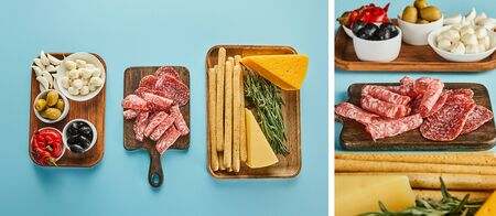 Collage of antipasto ingredients on boards on blue, panoramic shot Archivio Fotografico