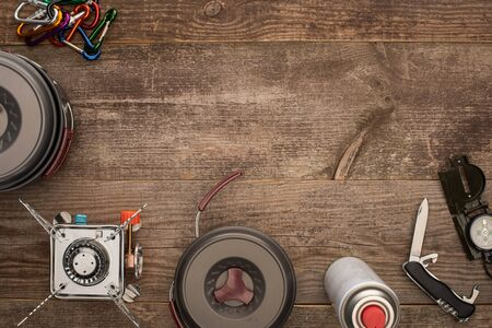top view of hiking dishes, gas burner and travel kit on wooden surface Stock Photo