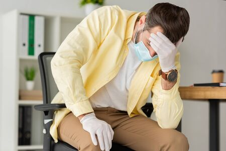 depressed businessman in latex gloves and medical mask holding hand on forehead while sitting in office