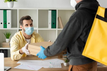 partial view of food delivery man giving pizza boxes to businessman in medical mask and latex gloves