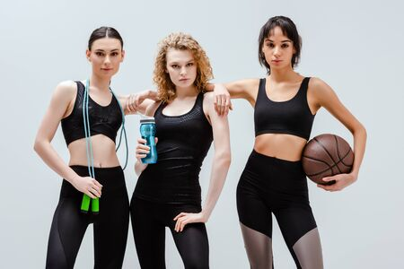attractive and multicultural girls standing with sport equipment isolated on white Фото со стока