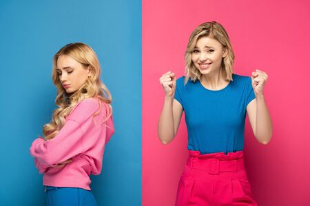 Cheerful woman showing yeah gesture near sad blonde sister on pink and blue background