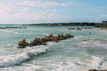 wet rocks in mediterranean sea against blue sky