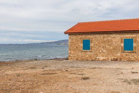 house near mediterranean sea against sky with clouds Imagens