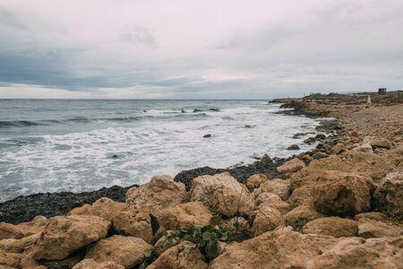 tranquil coastline with stones near blue sea