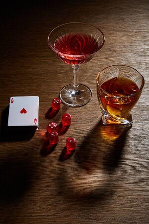high angle view of glasses of cognac and cocktail near deck of cards and dice on wooden background Foto de archivo