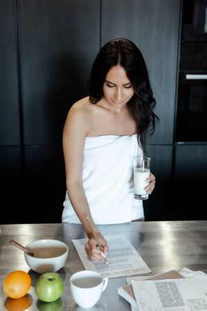 attractive woman in towel doing paperwork during breakfast on kitchen in morning