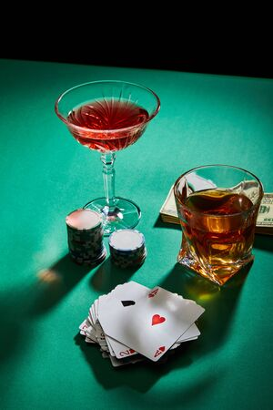 high angle view of glasses of cognac and cocktail near money, casino chips and playing cards on green surface isolated on black Foto de archivo