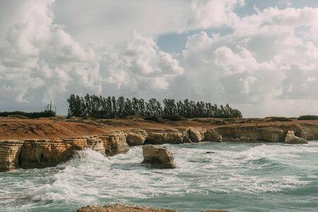 coastline of mediterranean sea against sky with white clouds