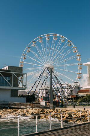 ferris wheel near building and mediterranean sea Imagens