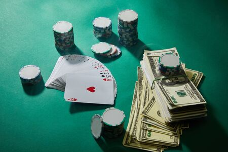 high angle view of playing cards, casino tokens and dollar banknotes on green background