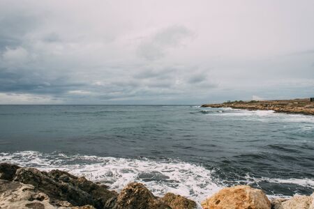 coastline with rocks near mediterranean sea against sky with clouds