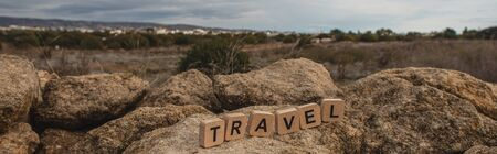 panoramic shot of wooden cubes with travel lettering on stones against sky Stok Fotoğraf