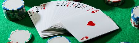 high angle view of pack of cards with casino chips on green background, panoramic shot Foto de archivo