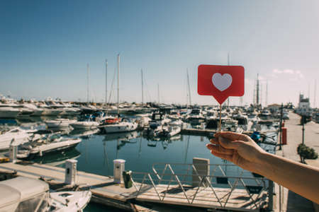 cropped view of woman holding red heart on stick as like near docked ships in mediterranean sea