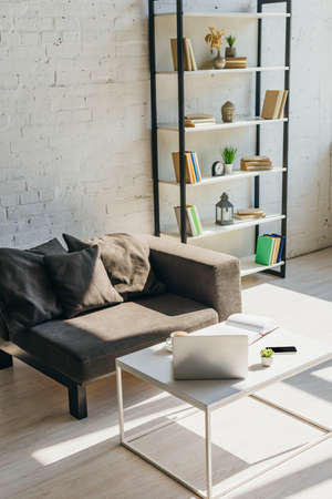 living room with grey sofa, shelf and table with laptop, smartphone and notepad in sunlight Reklamní fotografie