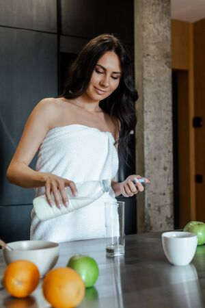 beautiful woman in towel pouring milk into glass for breakfast on kitchen in morning, selective focus