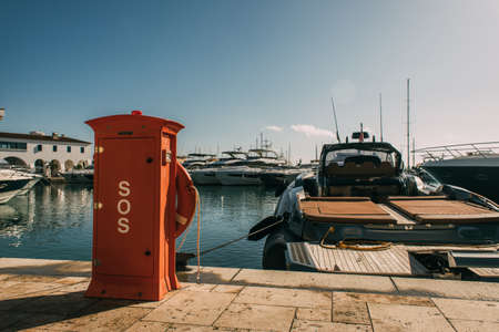 red booth with sos lettering near yachts in mediterranean sea