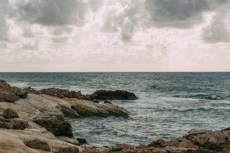 coastline near mediterranean sea against grey sky with clouds