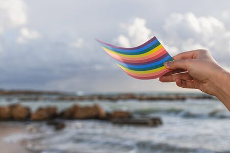 cropped view of woman holding rainbow lgbt flag near sea