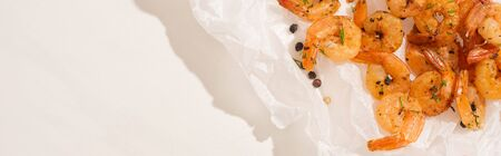 top view of fried shrimps on parchment paper with pepper on white background, panoramic shot