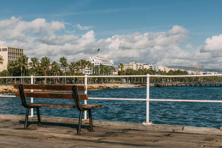 wooden bench near blue mediterranean sea in cyprus 免版税图像