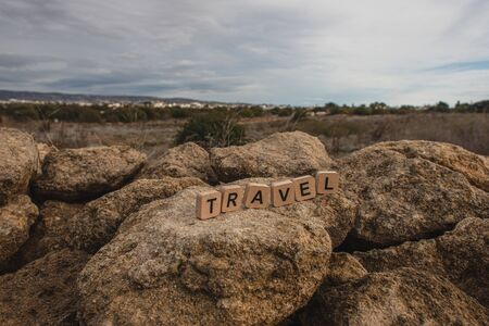 wooden cubes with travel lettering on rocks against sky