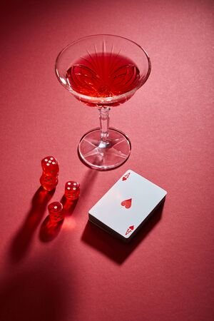 high angle view of glass of cocktail near deck of cards and dice on red background Foto de archivo