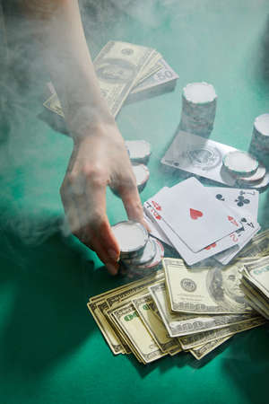 cropped view of female hand with casino tokens, playing cards and money with smoke around on green background 版權商用圖片