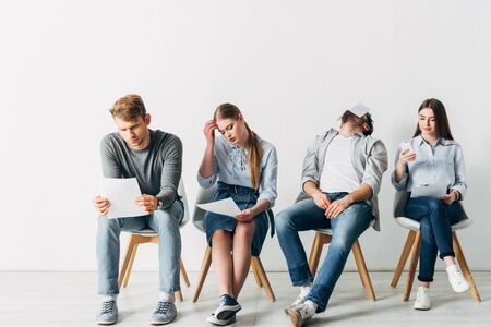 Group of young employees with resume using smartphones in office