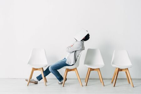 Side view of employee with crossed arms covering face with laptop on chair Фото со стока