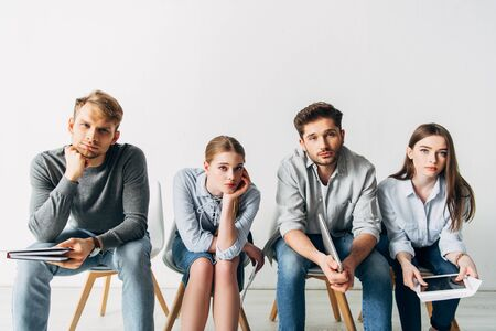 Group of young candidates with resume and gadgets looking at camera in office Фото со стока