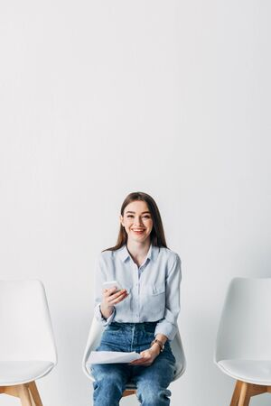 Smiling employee looking at camera while holding smartphone and resume in office Фото со стока