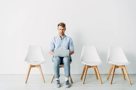 Handsome employee using laptop near resume and smartphone on chair in office